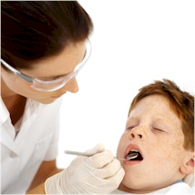 a dentist examining a child's mouth