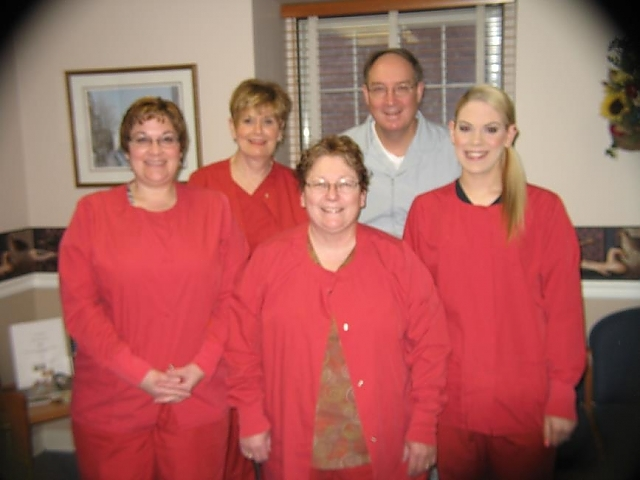 doctor cooper and four dental assistants dressed in red